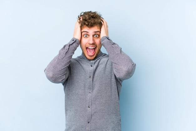Jeune homme caucasien cheveux bouclés blonds crier, très excité, passionné, satisfait de quelque chose.