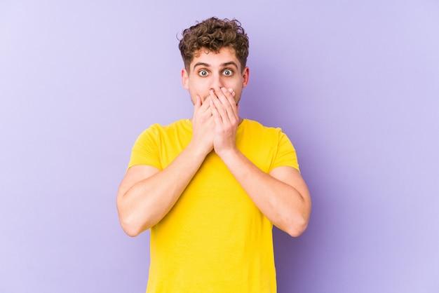 Jeune homme caucasien cheveux bouclés blonds isolé choqué couvrant la bouche avec les mains.