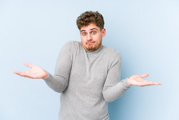 Jeune homme caucasien cheveux bouclés blonds isolé doutant et haussant les épaules en remettant en question le geste.