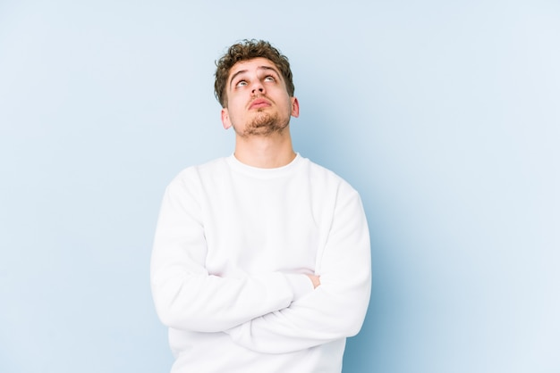Jeune homme caucasien cheveux bouclés blonds isolé fatigué d'une tâche répétitive.