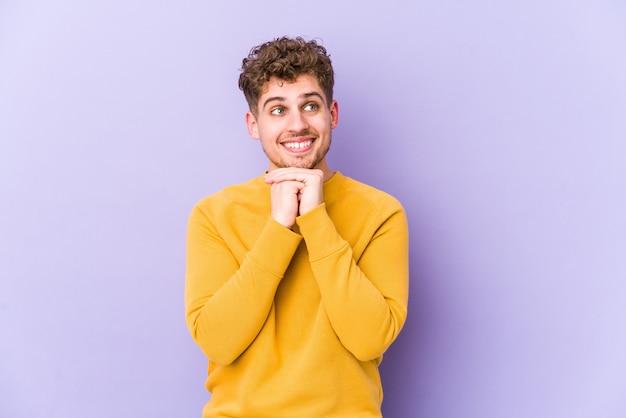 Jeune homme caucasien cheveux bouclés blonds isolé garde les mains sous le menton, regarde joyeusement de côté.
