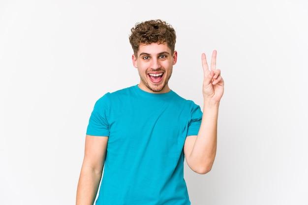 Jeune homme caucasien cheveux bouclés blonds isolé joyeux et insouciant montrant un symbole de paix avec les doigts.
