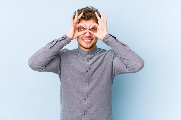 Jeune homme caucasien cheveux bouclés blonds isolé montrant signe correct sur les yeux
