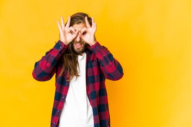Jeune homme caucasien cheveux longs isolé exprimant des émotions
