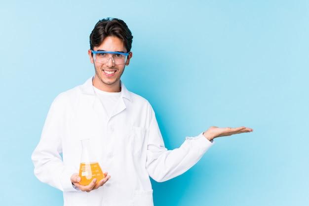 Jeune homme caucasien cientific isolé montrant un espace de copie sur une paume et tenant une autre main sur la taille.