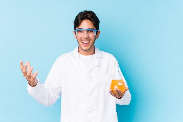 Jeune homme caucasien cientific isolé recevant une agréable surprise, excité et levant les mains.