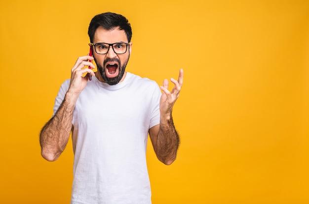 Jeune homme caucasien en colère, frustré et furieux avec son téléphone portable, en colère contre le service client. isolé sur fond jaune.