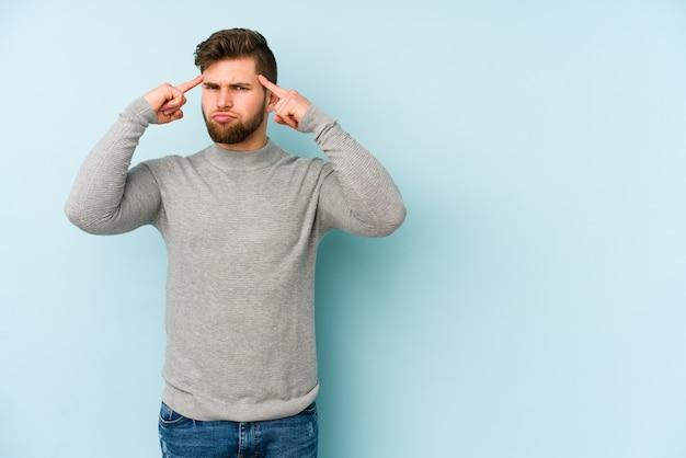 Jeune homme caucasien concentré sur une tâche, gardant l'index pointant la tête.