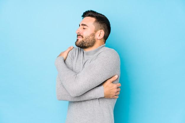 Jeune homme caucasien contre un mur bleu isolé câlins, souriant insouciant et heureux.