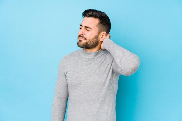 Jeune homme caucasien contre un mur bleu isolé souffrant de douleurs au cou en raison d'un mode de vie sédentaire.