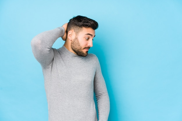 Jeune homme caucasien contre un mur bleu isolé toucher l'arrière de la tête, penser et faire un choix.