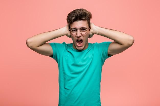 Jeune homme caucasien cool couvrant les oreilles avec les mains en essayant de ne pas entendre un son trop fort