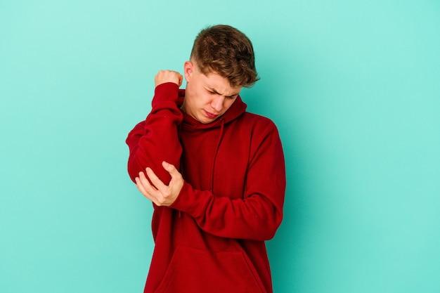 Jeune homme caucasien sur le coude de massage bleu, souffrant après un mauvais mouvement.