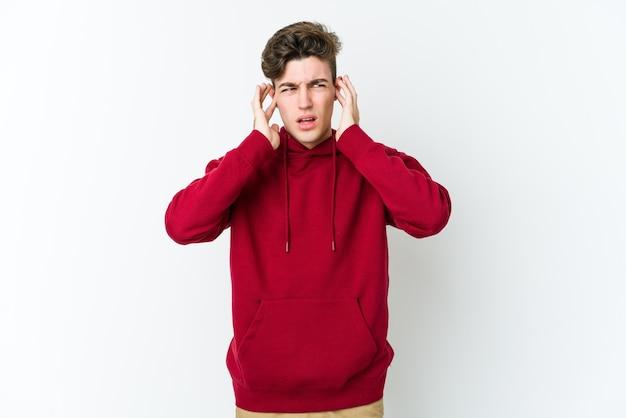 Jeune homme caucasien couvrant les oreilles avec les doigts, stressé et désespéré par un bruit ambiant.