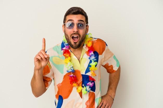 Jeune homme caucasien dansant sur une fête hawaïenne isolée sur fond blanc ayant une idée, un concept d'inspiration.