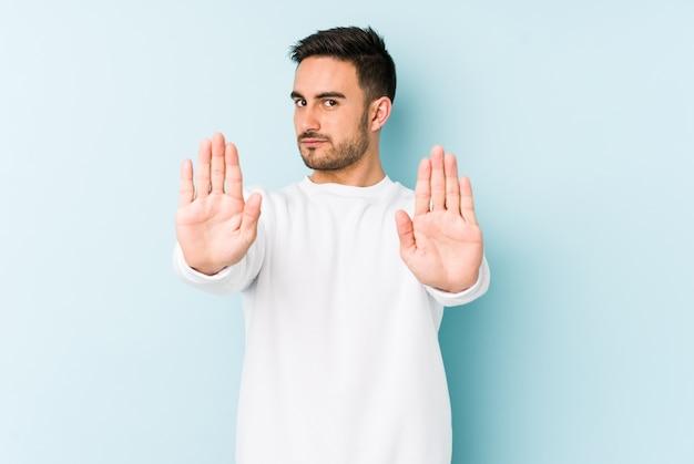 Jeune homme caucasien debout avec la main tendue montrant le panneau d'arrêt, vous empêchant.