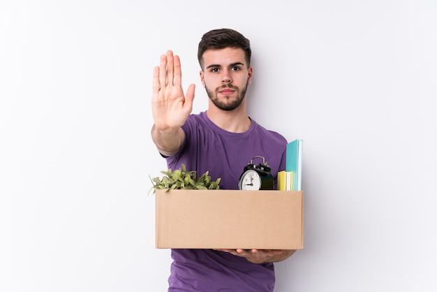 Jeune homme caucasien déménageant une nouvelle maison isolée debout avec la main tendue montrant le panneau d'arrêt, vous empêchant.