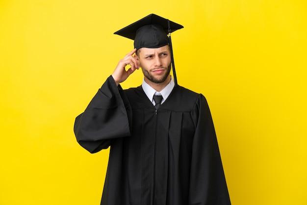 Jeune homme caucasien diplômé universitaire isolé sur fond jaune ayant des doutes et avec une expression de visage confuse