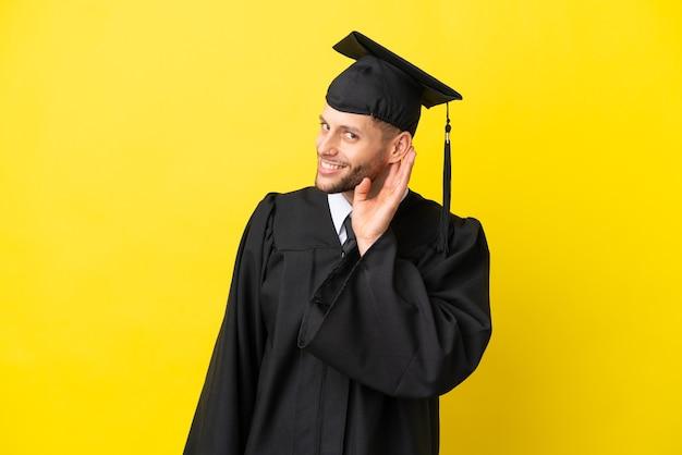 Jeune homme caucasien diplômé universitaire isolé sur fond jaune écoutant quelque chose en mettant la main sur l'oreille