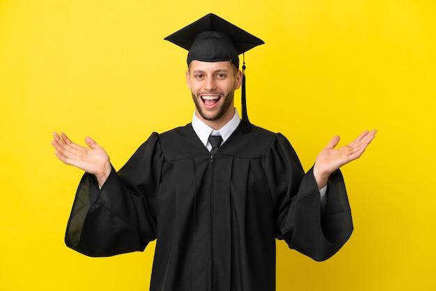 Jeune homme caucasien diplômé universitaire isolé sur fond jaune avec une expression faciale choquée