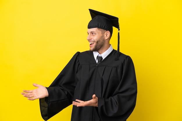 Jeune homme caucasien diplômé universitaire isolé sur fond jaune avec une expression faciale surprise