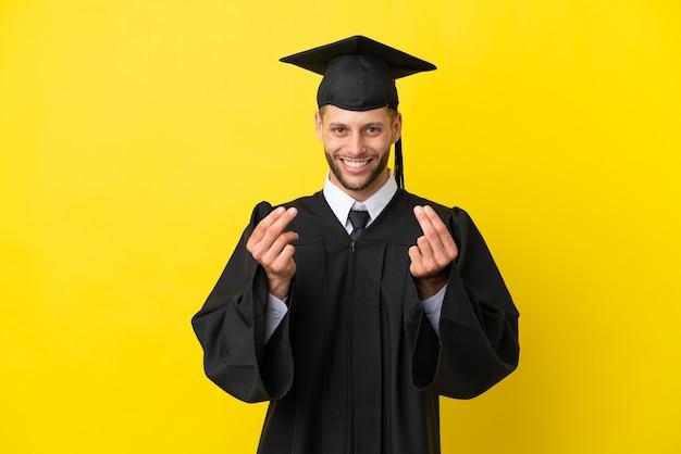 Jeune homme caucasien diplômé universitaire isolé sur fond jaune faisant un geste d'argent
