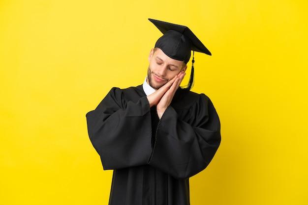 Jeune homme caucasien diplômé universitaire isolé sur fond jaune faisant un geste de sommeil dans une expression adorable