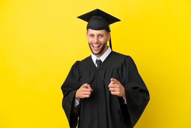 Jeune homme caucasien diplômé universitaire isolé sur fond jaune pointant vers l'avant et souriant