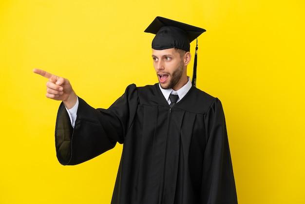 Jeune homme caucasien diplômé universitaire isolé sur fond jaune pointant vers l'extérieur