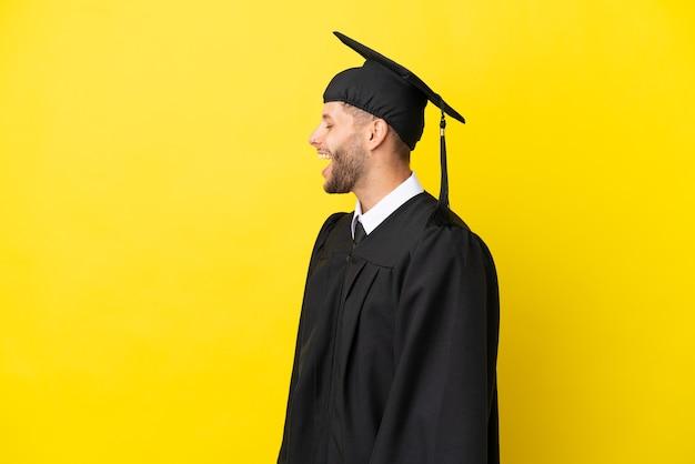 Jeune homme caucasien diplômé universitaire isolé sur fond jaune en riant en position latérale