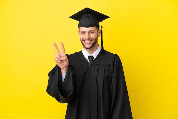 Jeune homme caucasien diplômé universitaire isolé sur fond jaune souriant et montrant le signe de la victoire