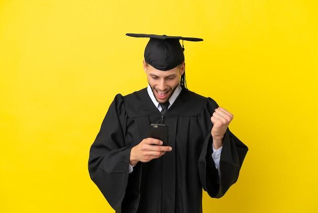 Jeune homme caucasien diplômé universitaire isolé sur fond jaune surpris et envoyant un message