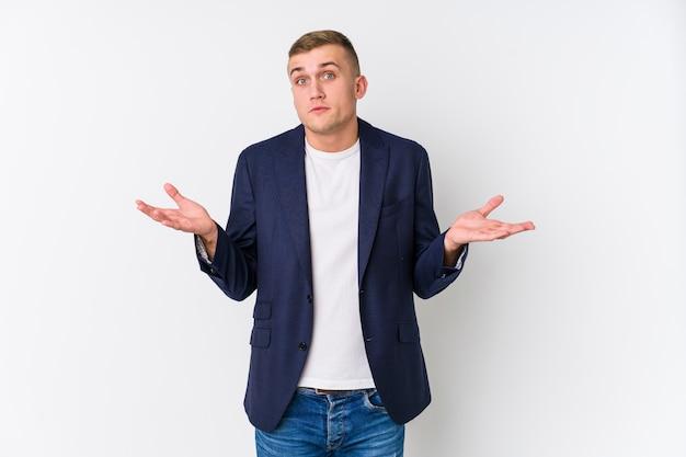 Jeune homme caucasien doutant et haussant les épaules en remettant en question le geste.