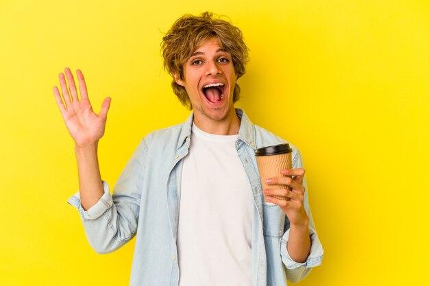 Jeune homme caucasien avec du maquillage tenant un café à emporter isolé sur fond jaune recevant une agréable surprise, excité et levant les mains.
