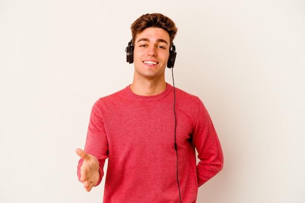 Jeune homme caucasien écoutant de la musique isolée sur fond blanc s'étendant la main à la caméra en geste de salutation.