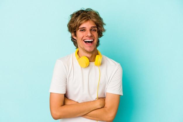 Jeune homme caucasien écoutant de la musique isolée sur fond bleu en riant et en s'amusant.
