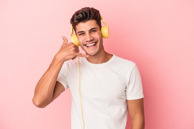 Jeune homme caucasien écoutant de la musique isolée sur fond rose montrant un geste d'appel de téléphone portable avec les doigts.