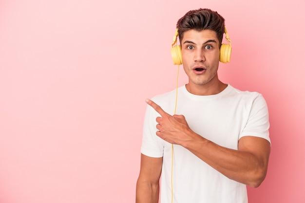 Jeune homme caucasien écoutant de la musique isolée sur fond rose pointant vers le côté