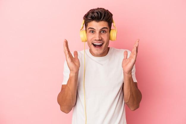 Jeune homme caucasien écoutant de la musique isolée sur fond rose surpris et choqué.