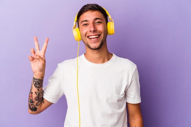 Jeune homme caucasien écoutant de la musique isolée sur fond violet joyeux et insouciant montrant un symbole de paix avec les doigts.