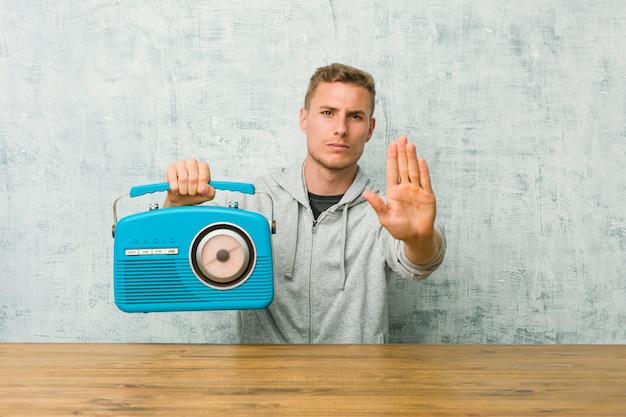 Jeune homme caucasien, écoutant la radio debout avec la main tendue montrant le panneau d'arrêt, vous empêchant.