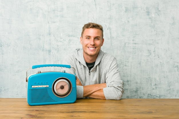 Jeune homme caucasien écoutant la radio heureux, souriant et joyeux.