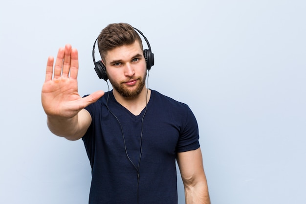 Jeune homme caucasien, écouter de la musique debout avec la main tendue montrant le panneau d'arrêt, vous empêchant.