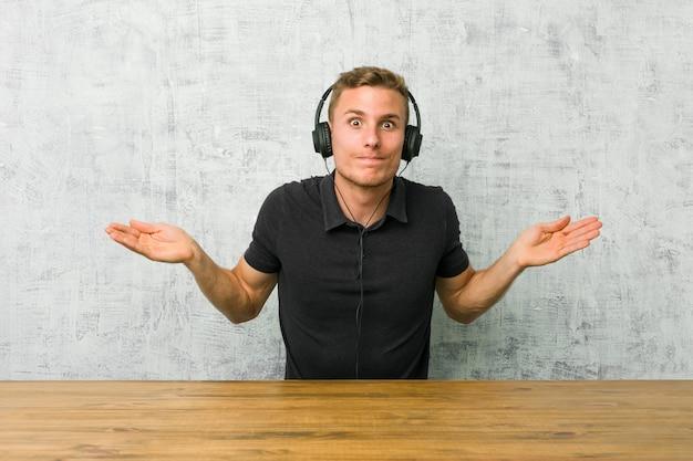 Jeune homme caucasien, écouter de la musique avec des écouteurs doutant et haussant les épaules en geste de remise en question.