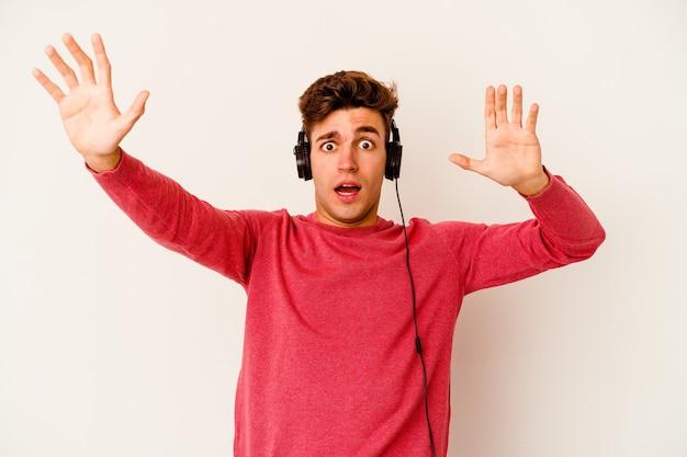 Jeune homme caucasien, écouter de la musique isolé sur un mur blanc étant choqué en raison d'un danger imminent