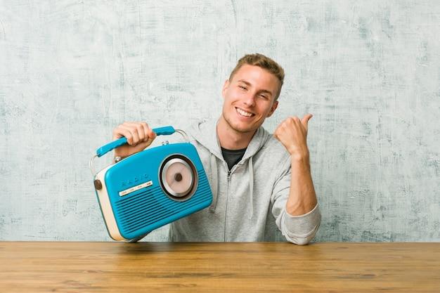 Jeune homme caucasien, écouter la radio en souriant et en levant le pouce vers le haut