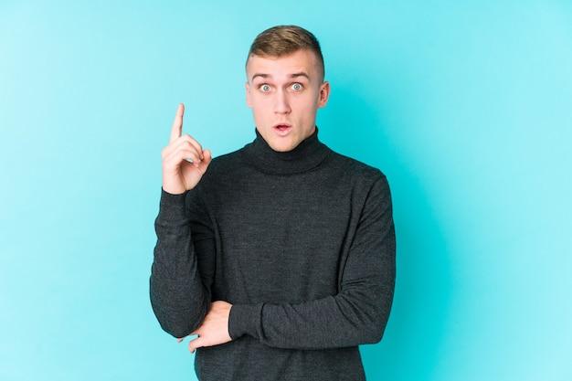 Jeune homme caucasien sur un espace bleu ayant une excellente idée, concept de créativité.