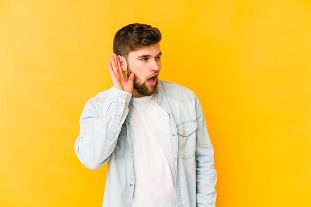 Jeune homme caucasien essayant d'écouter un commérage.