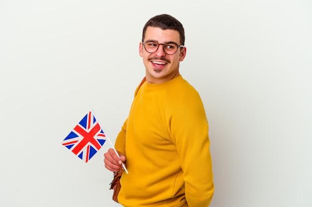 Jeune homme caucasien étudiant l'anglais sur blanc regarde de côté souriant, joyeux et agréable.