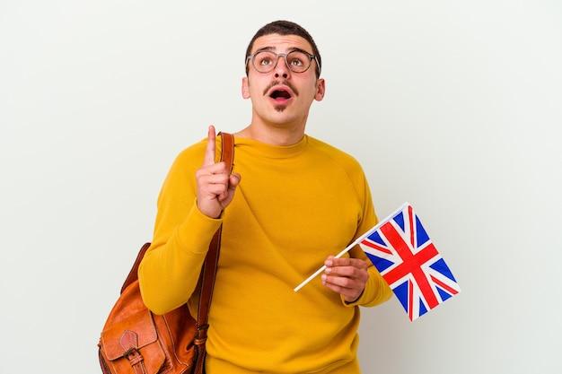 Jeune homme caucasien étudiant l'anglais isolé sur un mur blanc pointant vers le haut avec la bouche ouverte.